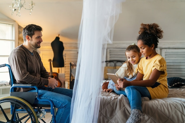Happy father with disability in wheelchair enjoying time with children at home. family, love, technology concept