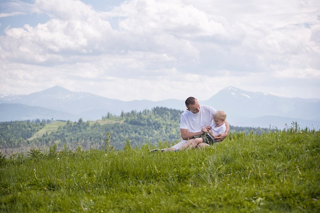 Happy father with his little son on his knees sits on grass in green forest at the mountains