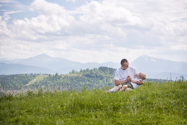 Happy father with his little son on his knees sits on meadow