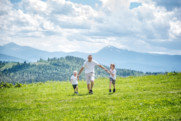 Happy father with his little sons on his knees sits on grass in green forest at the mountains