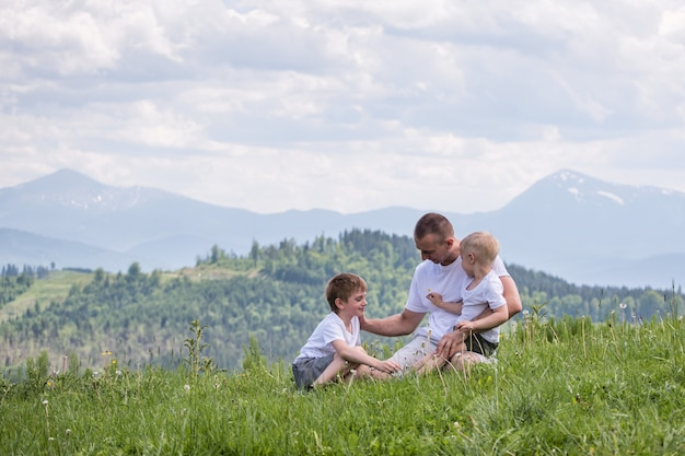 Happy father with his two young sons sitting the grass on a  of green forest, mountains and sky with clouds. friendship .