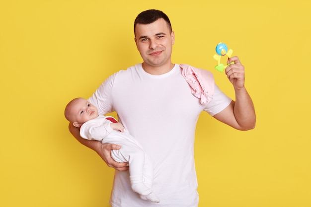 家で小さな赤ん坊の娘が一緒に遊んでいる幸せな父、黄色い壁の上に孤立してポーズをとっている間彼女の娘の世話をしているガラガラと若いお父さん。