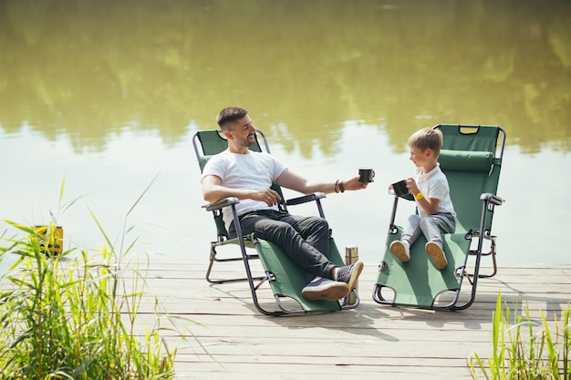 Happy father with little son resting by the lake sitting on comfortable chairs on a wooden pier. dad and child boy spend leisure time together outdoors. camp vacation in countryside. fathers day