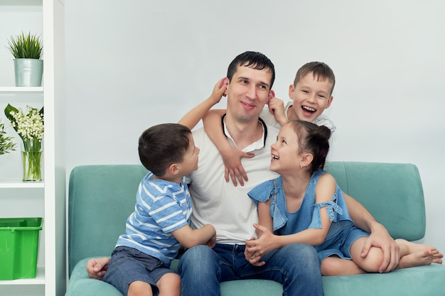 A happy father with many children and his children is sitting on a blue sofa