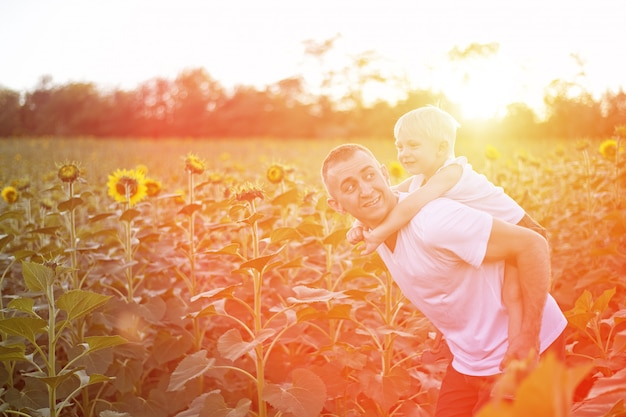 Happy father with son on back walking on field of blooming sunflowers