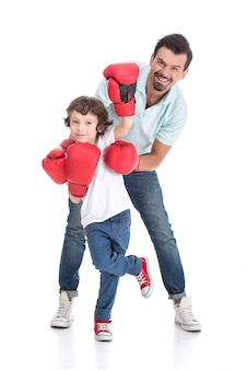 Happy father with son in boxing gloves.