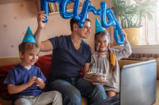 Happy father with two sibling celebrating birthday during internet party in quarantine time