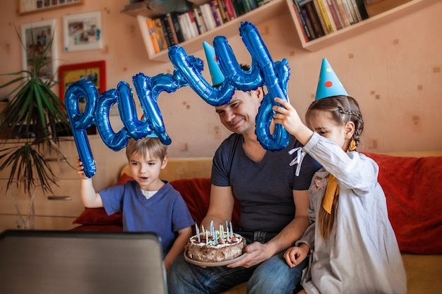Happy father with two sibling celebrating birthday via internet in quarantine time, self-isolation