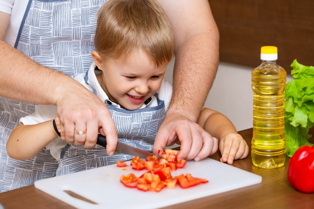 A happy father and a young son prepare a salad in the kitchen with vegetables.