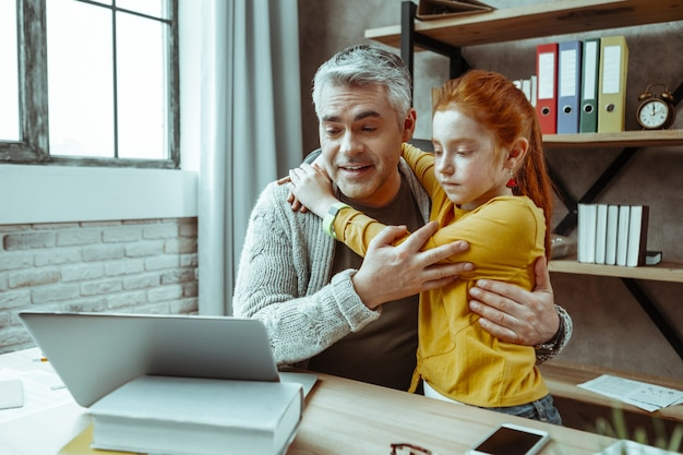 Happy fatherhood. positive cheerful man looking at the laptop screen while hugging his daughter