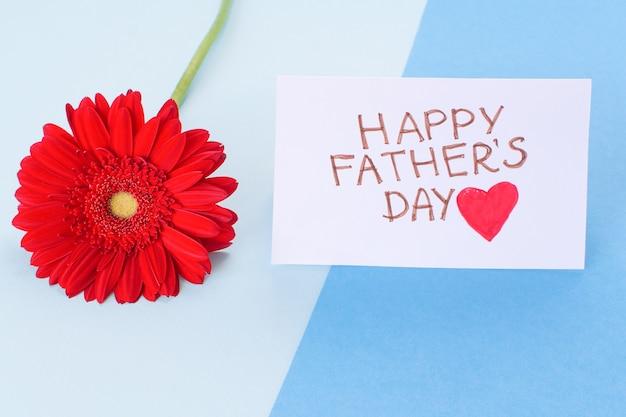 幸せな父の日。幸せな父の日と花の赤いガーベラの碑文とカード
