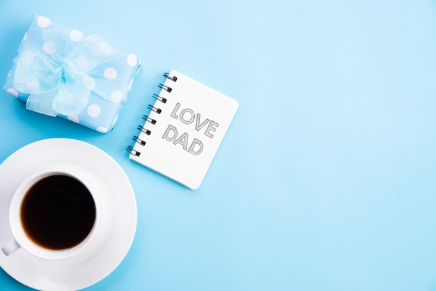 Happy fathers day concept. beautiful gift box, coffee mug with love dad text