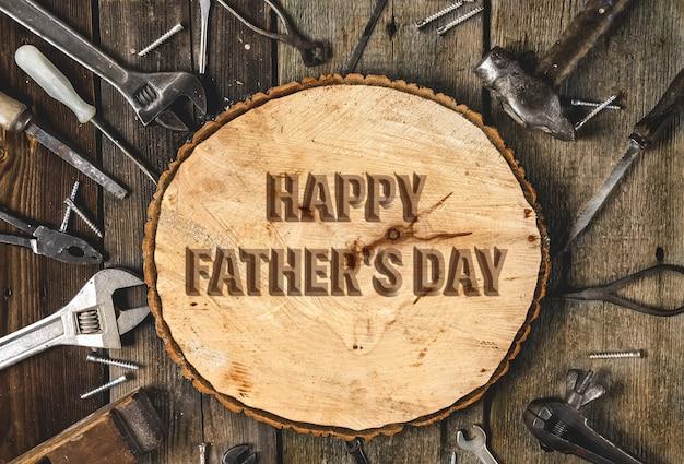 Поздравительный текст с днем отца на деревенском деревянном фоне в окружении различных инструментов