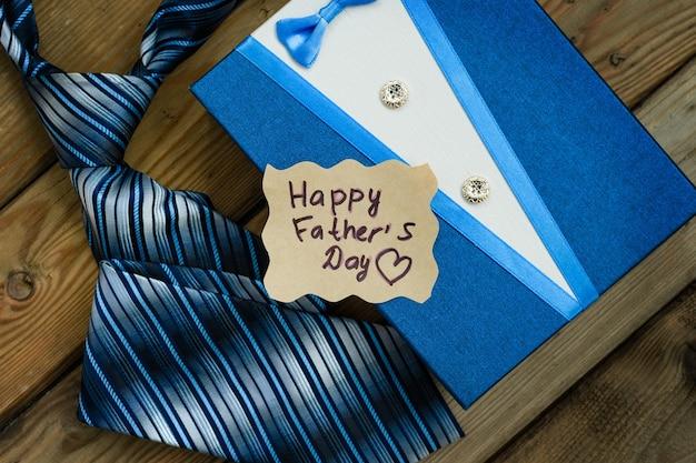 Коробка счастливого подарка дня отцов голубая с галстуком на деревенской деревянной предпосылке. открытка