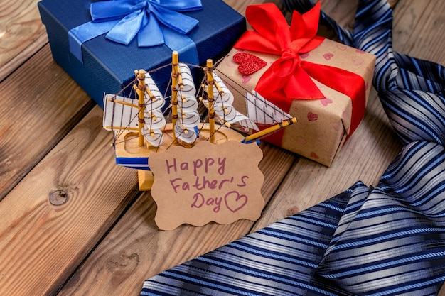 素朴な木の背景にネクタイと幸せな父の日ギフトボックス。グリーティングカード