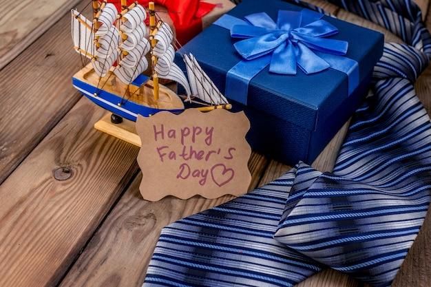 Счастливая подарочная коробка дня отцов с галстуком на деревенском деревянном фоне. открытка