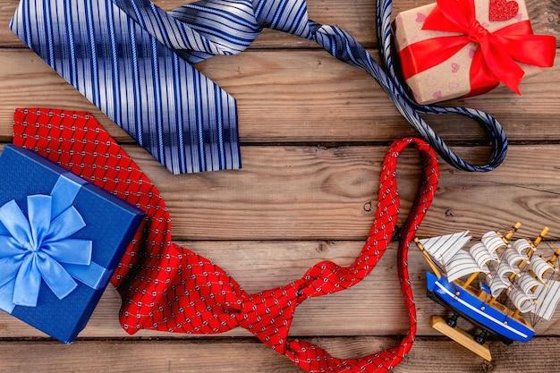 Счастливые подарочные коробки дня отцов с красными и синими связями на деревенской деревянной предпосылке. карточка вид сверху.