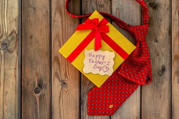 Счастливая коробка корабля подарка дня отцов с красной связью на деревенской деревянной предпосылке. открытка