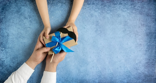 Happy fathers day gift in the hands of daughter and father on a blue background