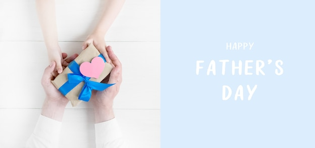 Happy fathers day greeting card gift in the hands of daughter and father on a white background