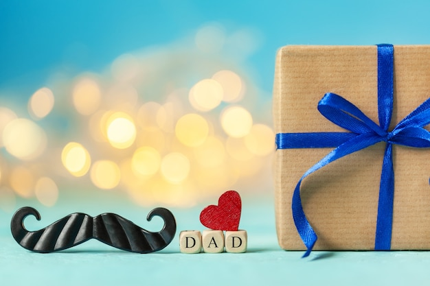 파란색 배경에 선물 상자와 레드 심장 해피 아버지의 날 인사말 카드.