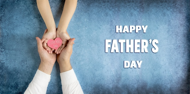 Happy fathers day greeting cardgift in the hands of daughter and father on a blue background