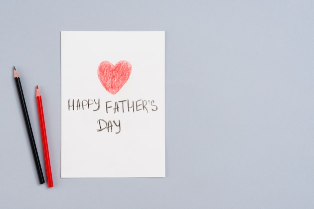 Happy fathers day inscription on paper with pencils