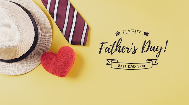 Happy fathers day inscription with colorful tie red heart and hat on pastel yellow background