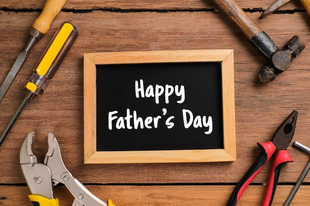 Happy fathers day text on chalkboard with side border of tools and ties on a rustic wood background