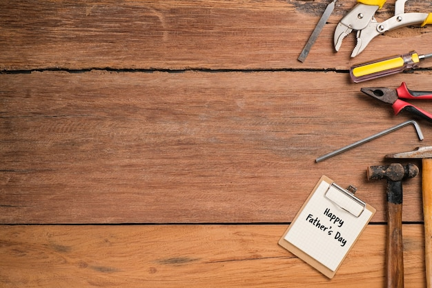 Happy fathers day text with side border of tools and ties on a rustic wood background