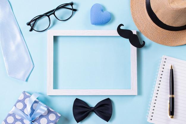幸せな父の日。明るい青色のパステル背景にネクタイ、ギフトボックス、帽子、額縁の平面図