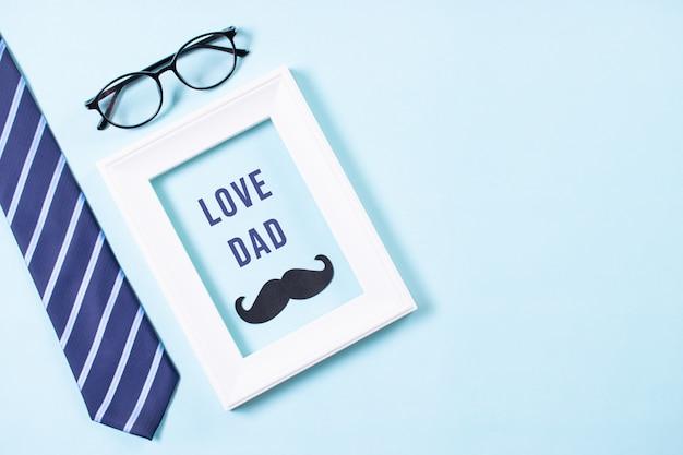 幸せな父の日。ネクタイ、口ひげ、メガネ、love dadテキスト付きの白い額縁の平面図。