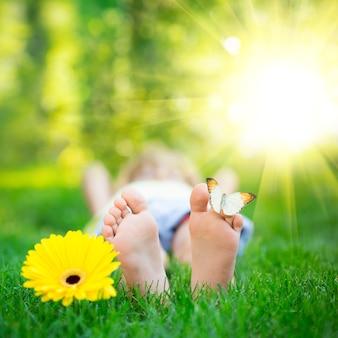 야외에서 나비와 함께 해피 피트 아이 봄 공원에서 재미 아이 녹색 잔디에 누워
