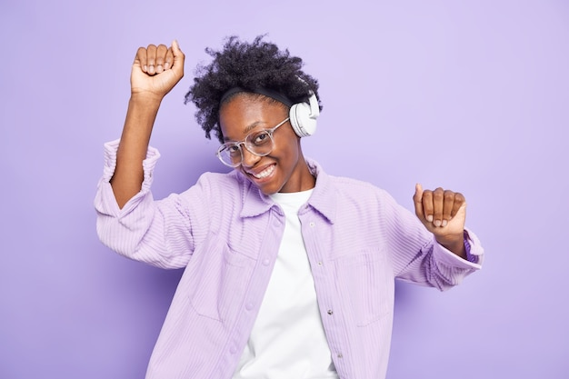Happy female afro american teenager with dark skin enjoys popular song in audio app moves with rhythm of music