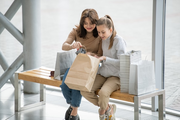 幸せな女性と彼女の娘が紙袋を開いて、父または友人への贈り物として買ったものを見て