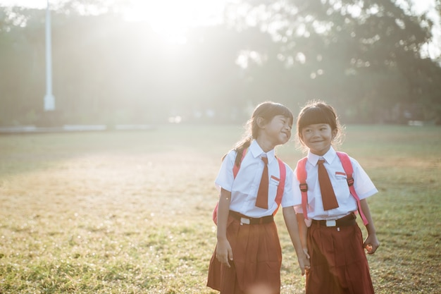 Happy female asian primary school student walk together