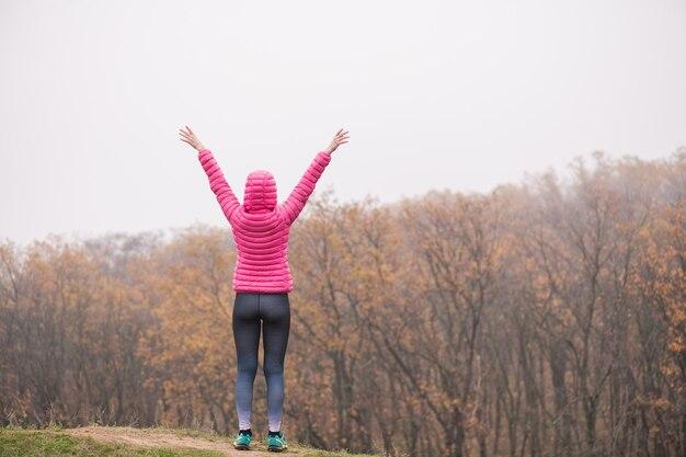 霧の森の背景で彼女の手を上げるピンクのコートと幸せな女性の背面図