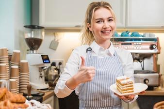 今すぐ登録親指を示す白いプレートに幸せな女性パン屋持株ペストリースライス