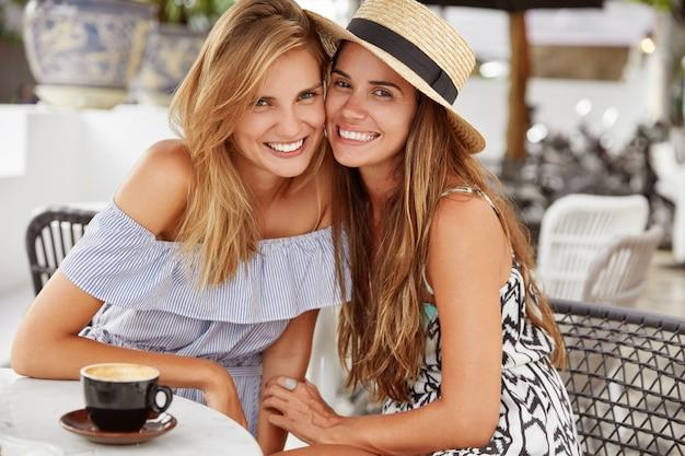 Счастливые лучшие подруги сидят в ресторане на открытом воздухе