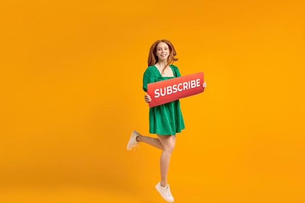 Happy female blogger просит подписаться на канал для видеоблогов. рыжая дама в зеленом платье эмоционально улыбается в камеру, прыгает. изолированные на желтом фоне в студии