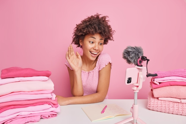 Happy female blogger meets her followers online waves palm in hello gesture smiles positively poses near folded clothes records video about domestic work and housekeeping makes notes in notepad