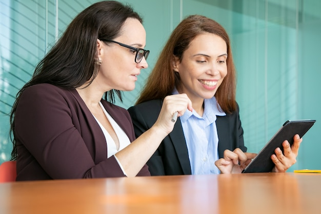 Happy female business colleagues using tablet together, looking at screen and smiling while sitting at table in meeting room.