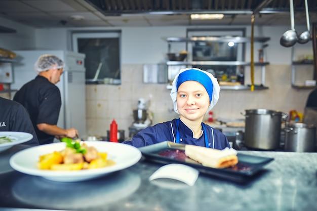 Счастливый женский шеф-повар готовит еду на кухне ресторана
