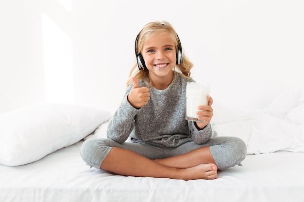 Счастливая девочка в наушниках держит стакан молока, показывая пальцем вверх жест