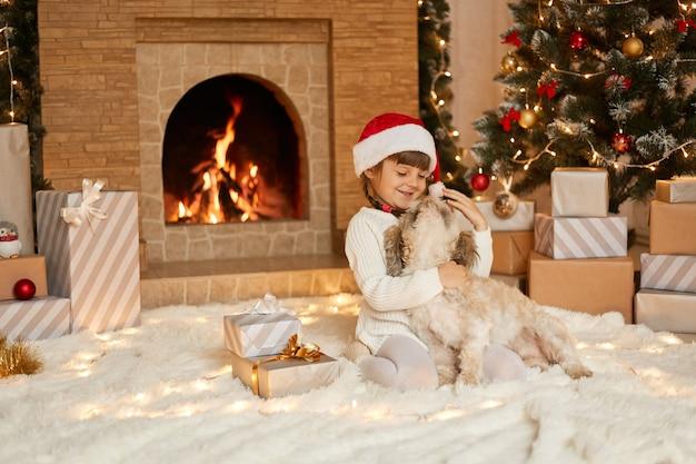 クリスマスイブに家で彼女のお気に入りのペットと遊ぶ幸せな女性の子供