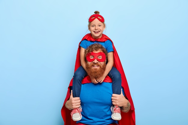 Happy female child sits on fathers shoulders, feels heroic and strong, wears red mask