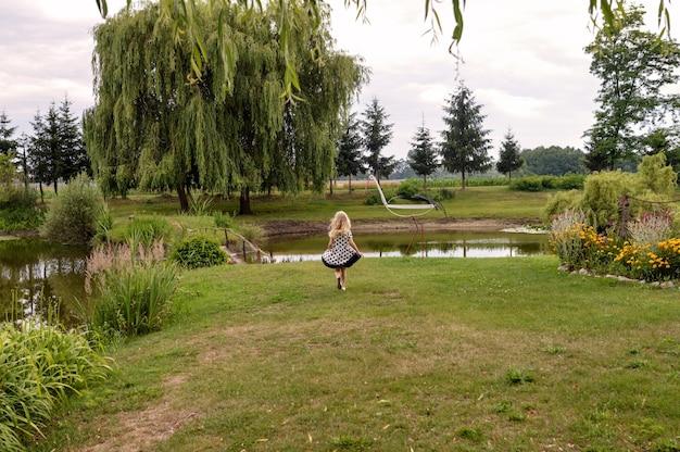 아름다운 정원에서 연못 앞에 서있는 행복 한 여자 아이