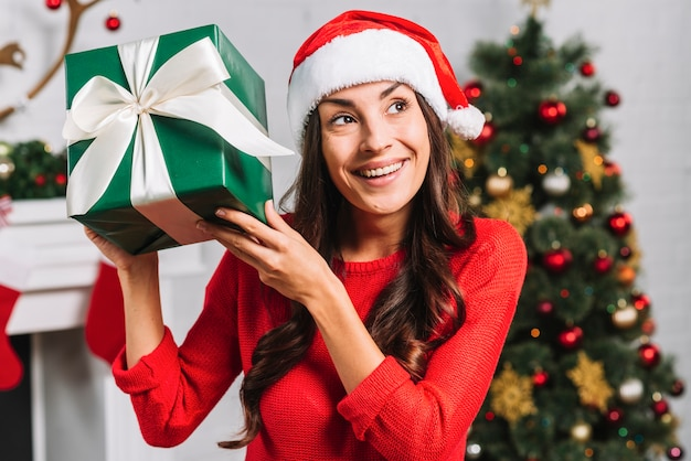 Happy female in christmas hat holding present box