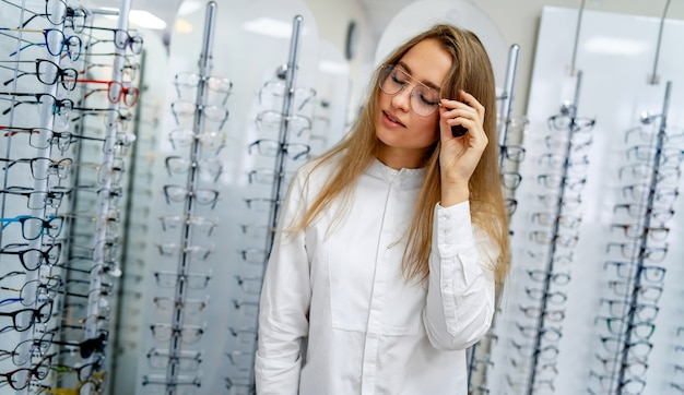 Happy female client or optician is standing with raw of glasses  in optical shop
