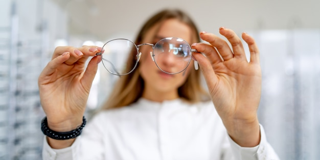 Happy female client or optician is standing with set of glasses